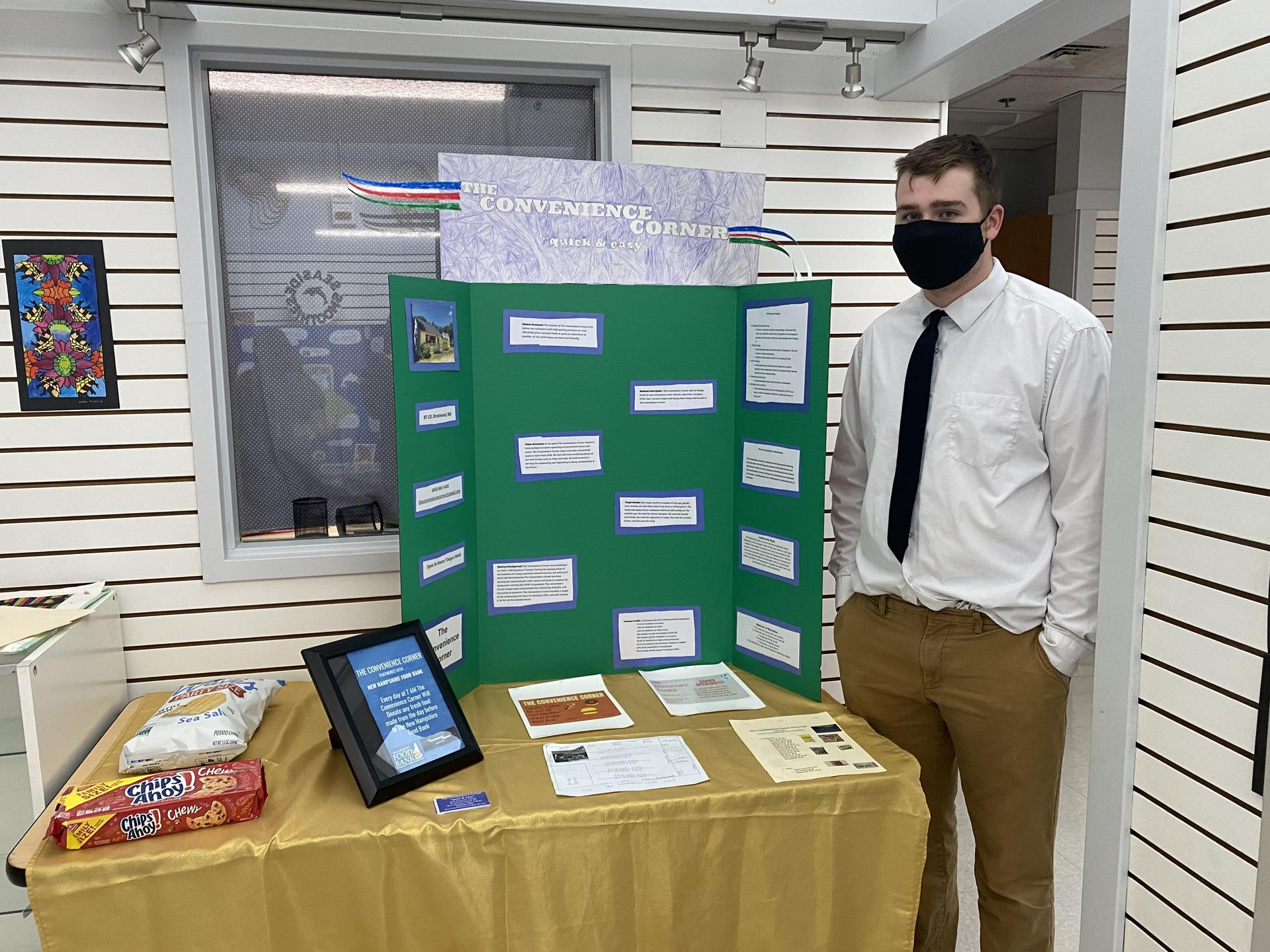 student in front of green presentation board