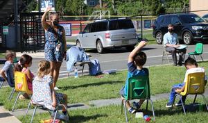 Photo of music teacher outside with kindergartners