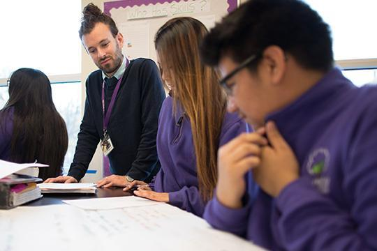 """High School teacher helping students with a math assigement in a Minneapolis school"""