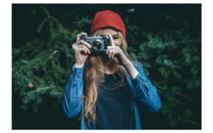 A woman holding a camera to her face.
