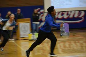 boy runs across gym floor holding water bottle