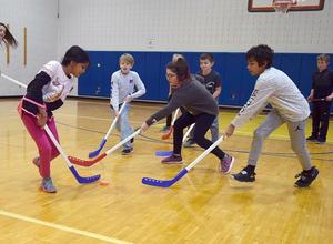 Elementary School students play hockey in their gym class.