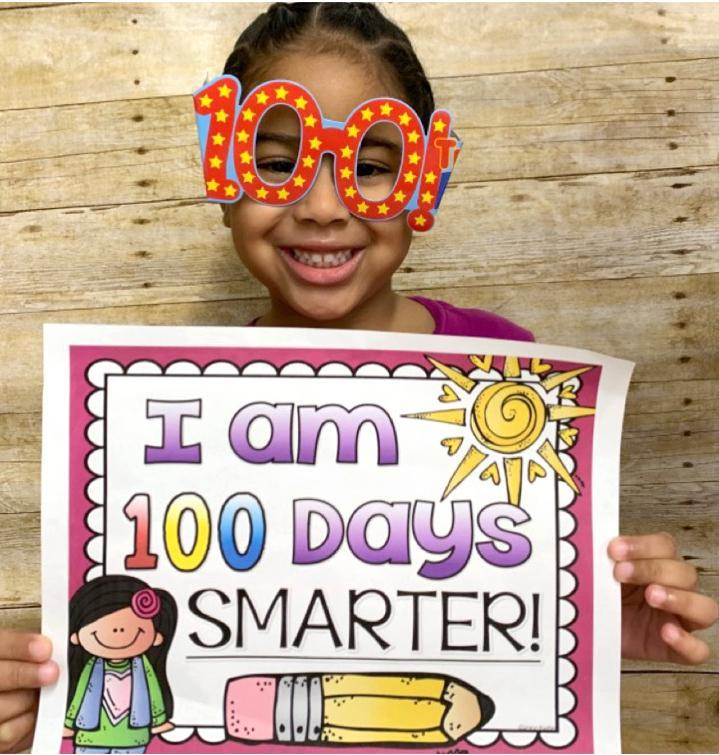 A pre-K student holds a sign that reads