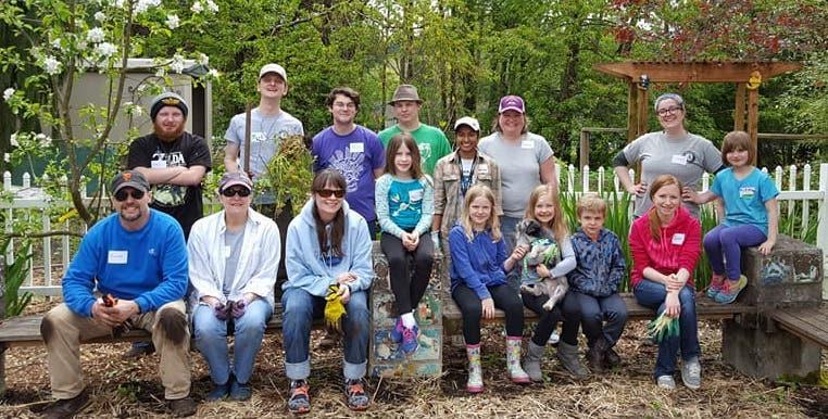 Americorps Members posing with family and friends during a service project