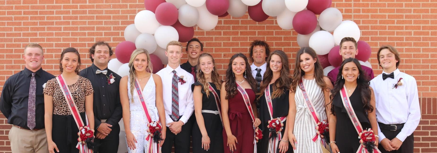 Homecoming court pose in front of balloon archway