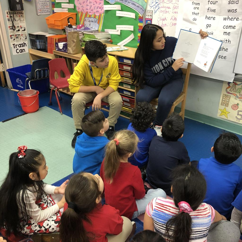two UHMS students reading a book to children seated on class rug