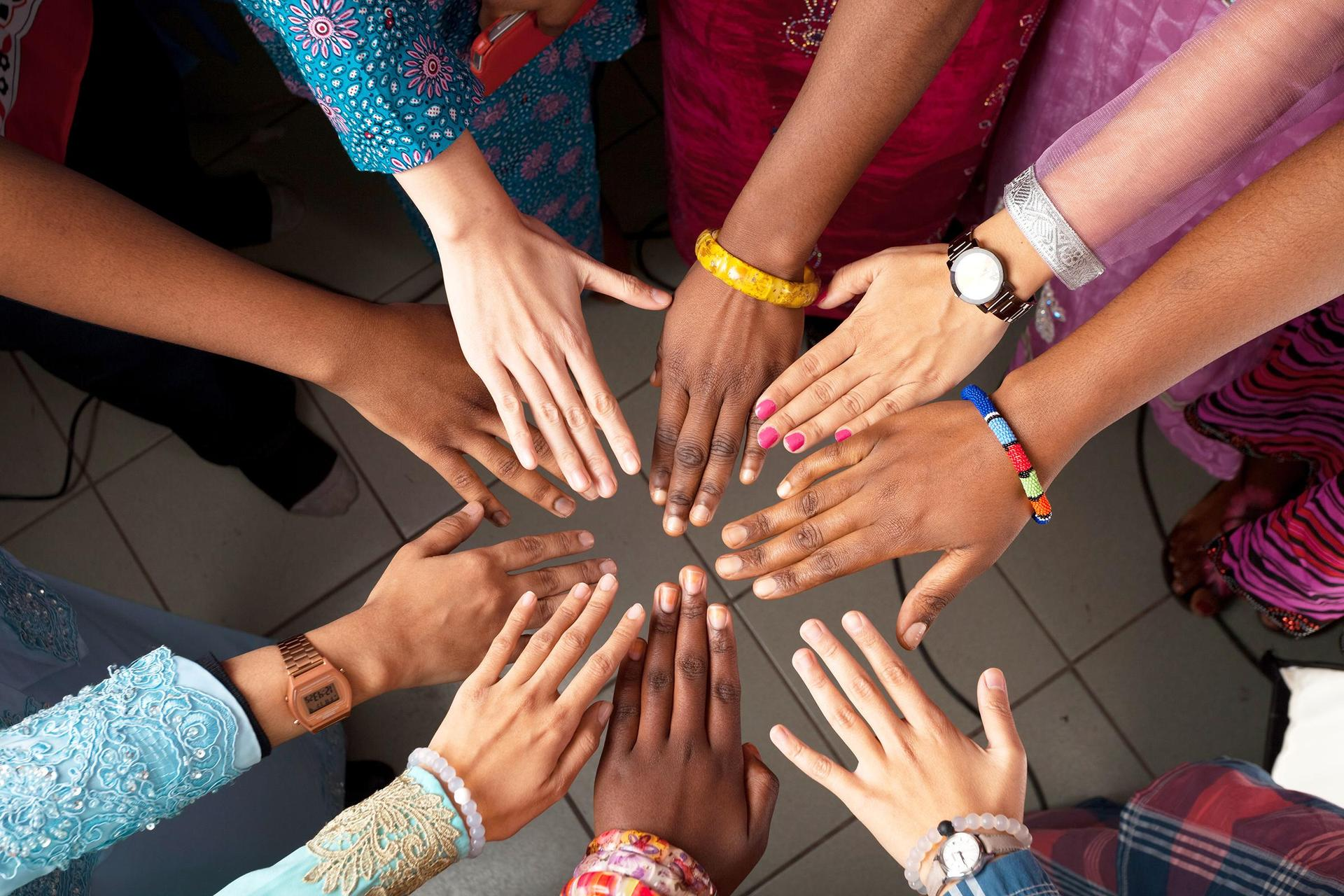Hands of happy group of people which stay together in circle