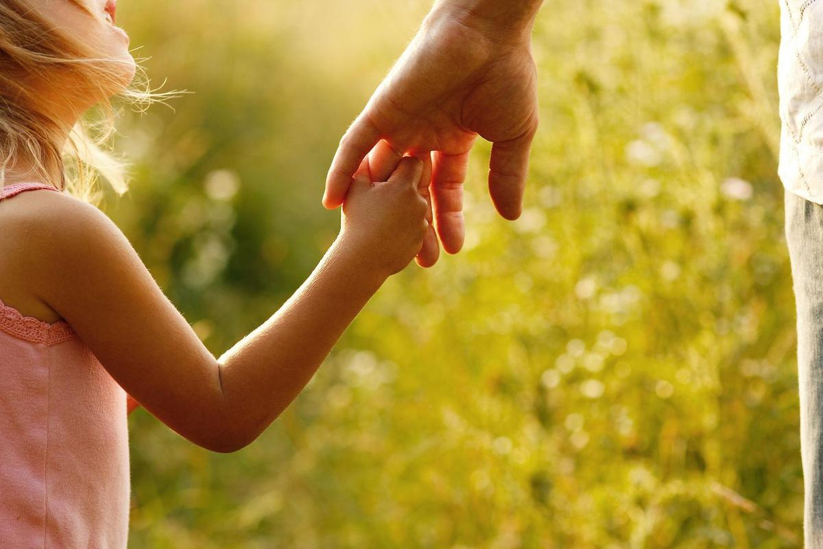 Child holding hand of an adult.