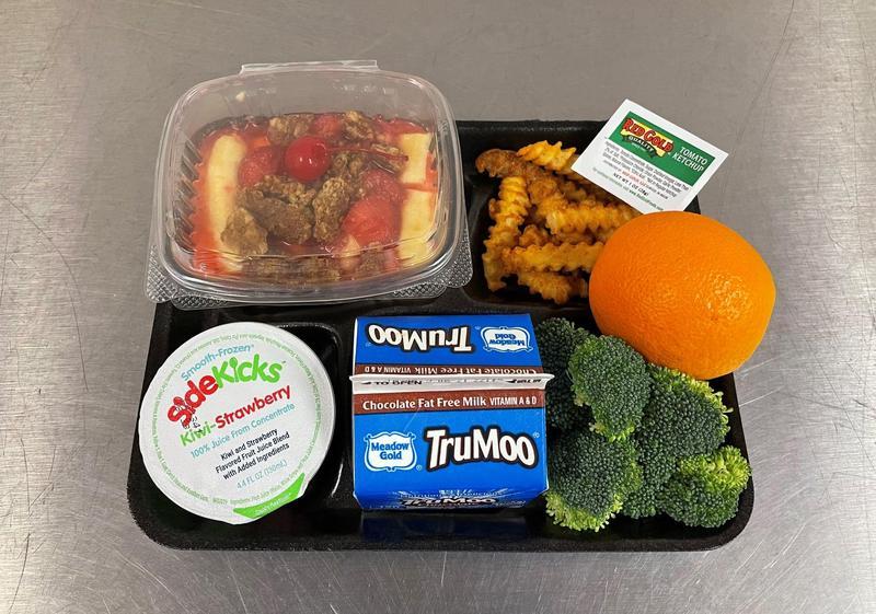 A lunch tray with yogurt parfait, fries, orange, broccoli, juice and milk