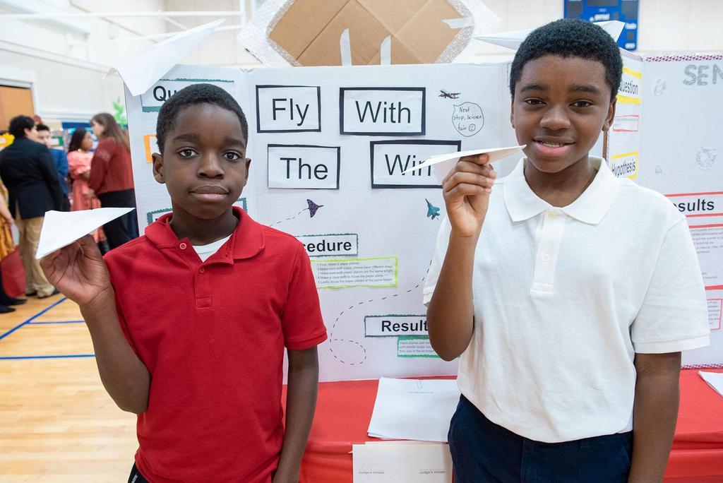 Two students stand in front of their project called Fly With the Wind
