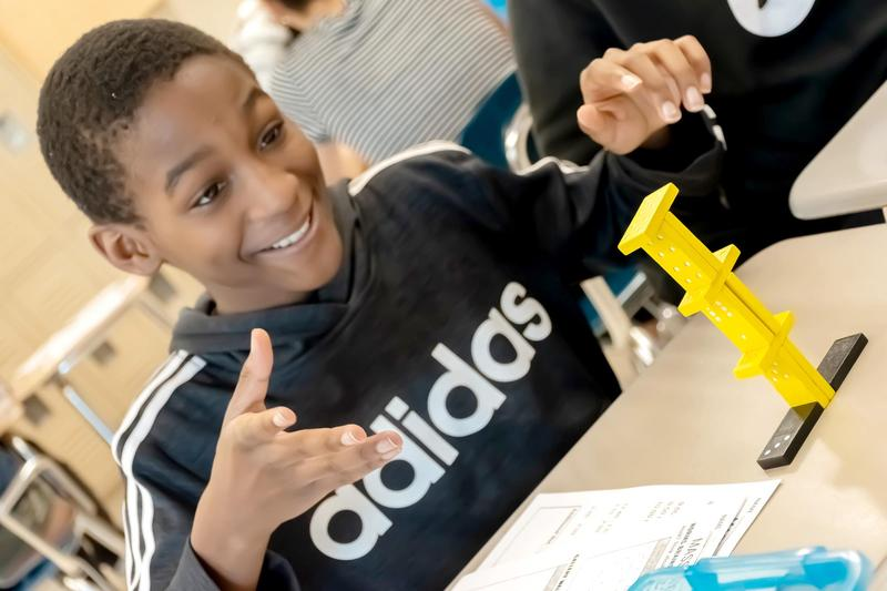 A student smiles as he unveils a kinetic sculpture he designed