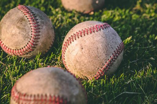 Photograph of 3 baseballs sitting in grass.