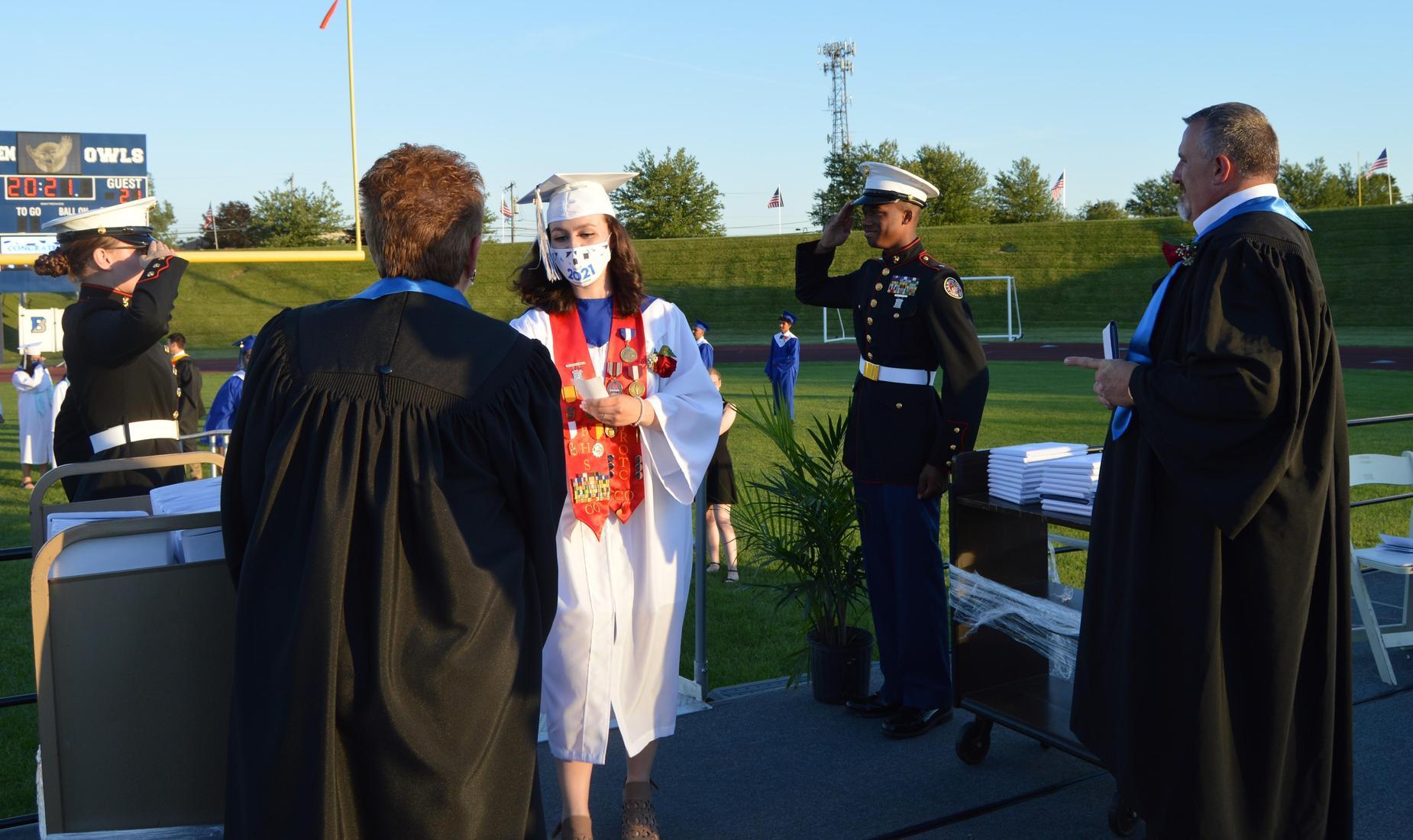 2 Bensalem High School MCJROTC cadets salute BHS senior as she receives her diploma