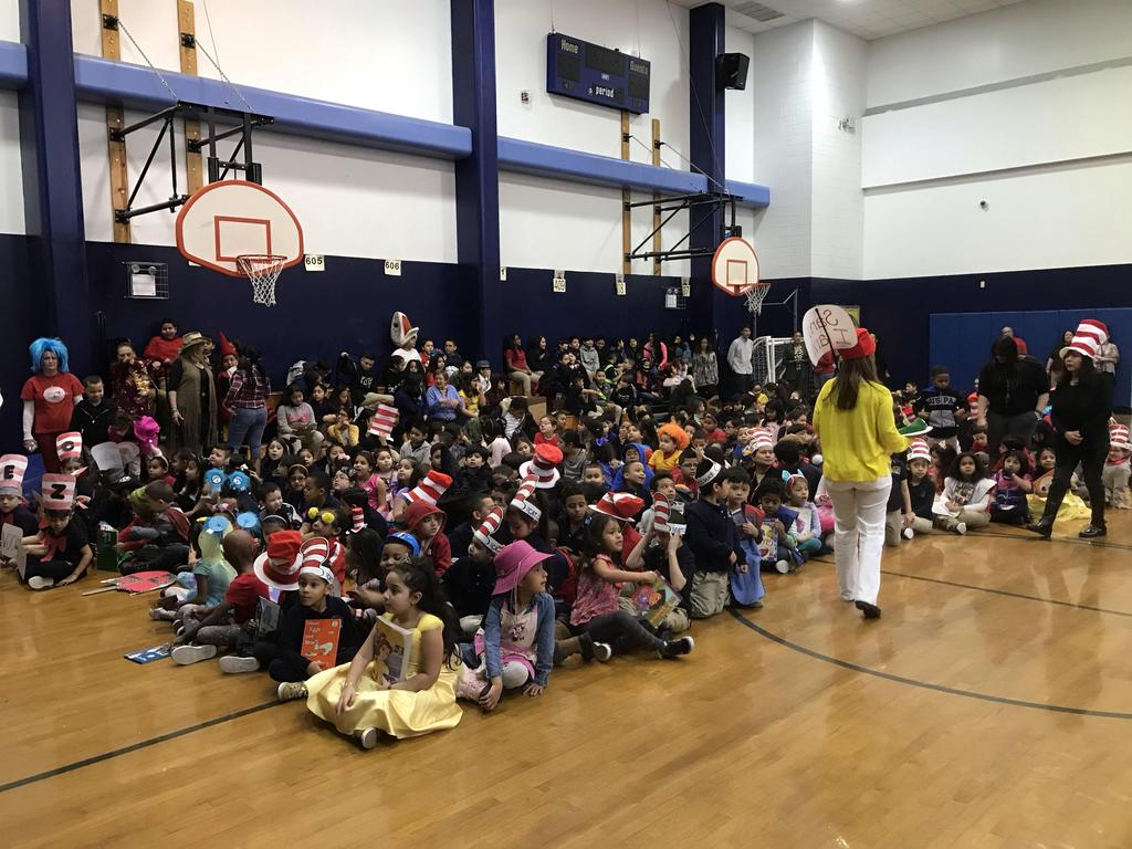 children on the gym floor sitting together dressed as their favorite characters