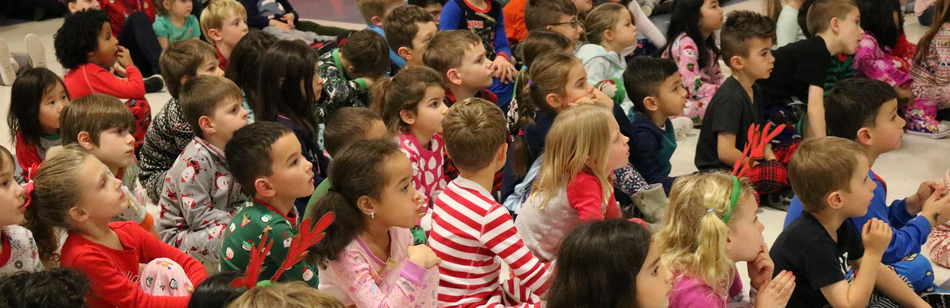 Kindergartners at Lincoln School are dressed in pajamas as they listen to principal Audrey Zavatz read The Polar Express.