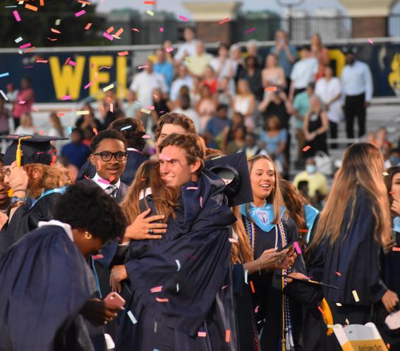 Group of students in graduation regalia hugging, confetti falling around them