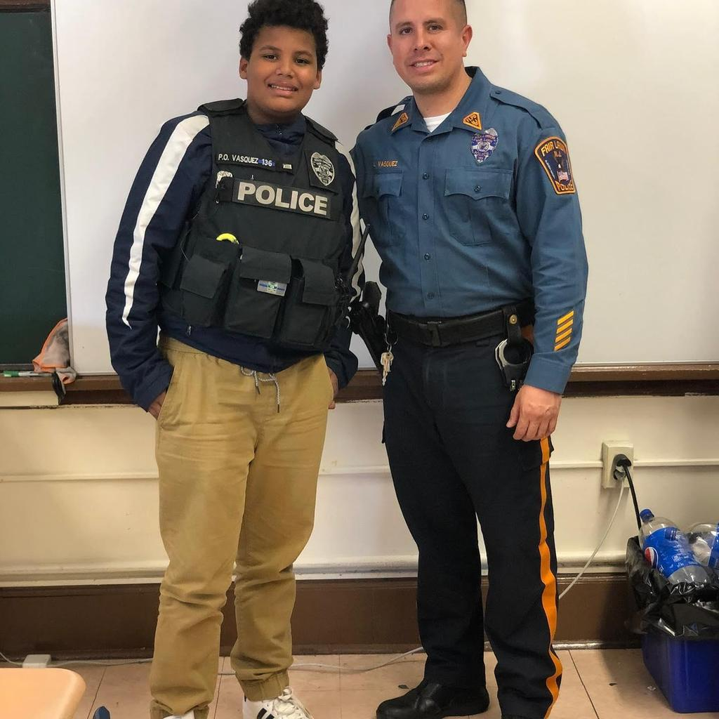 officer Vasquez with a male student who is wearing Vasquez' vest
