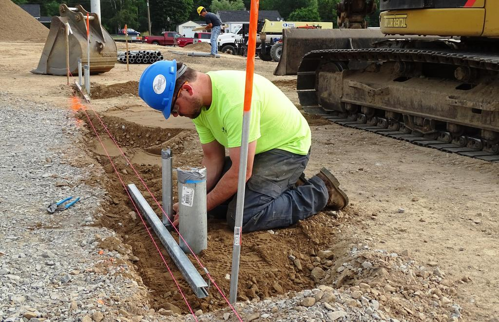 Captured in this snapshot is an electrician who is a member of electrical contractor Weydman Electric and Communications' electrical work crew. On July 11, 2019 this electrician was in the process of installing electrical power and communications lines at the feature field area on the main campus.