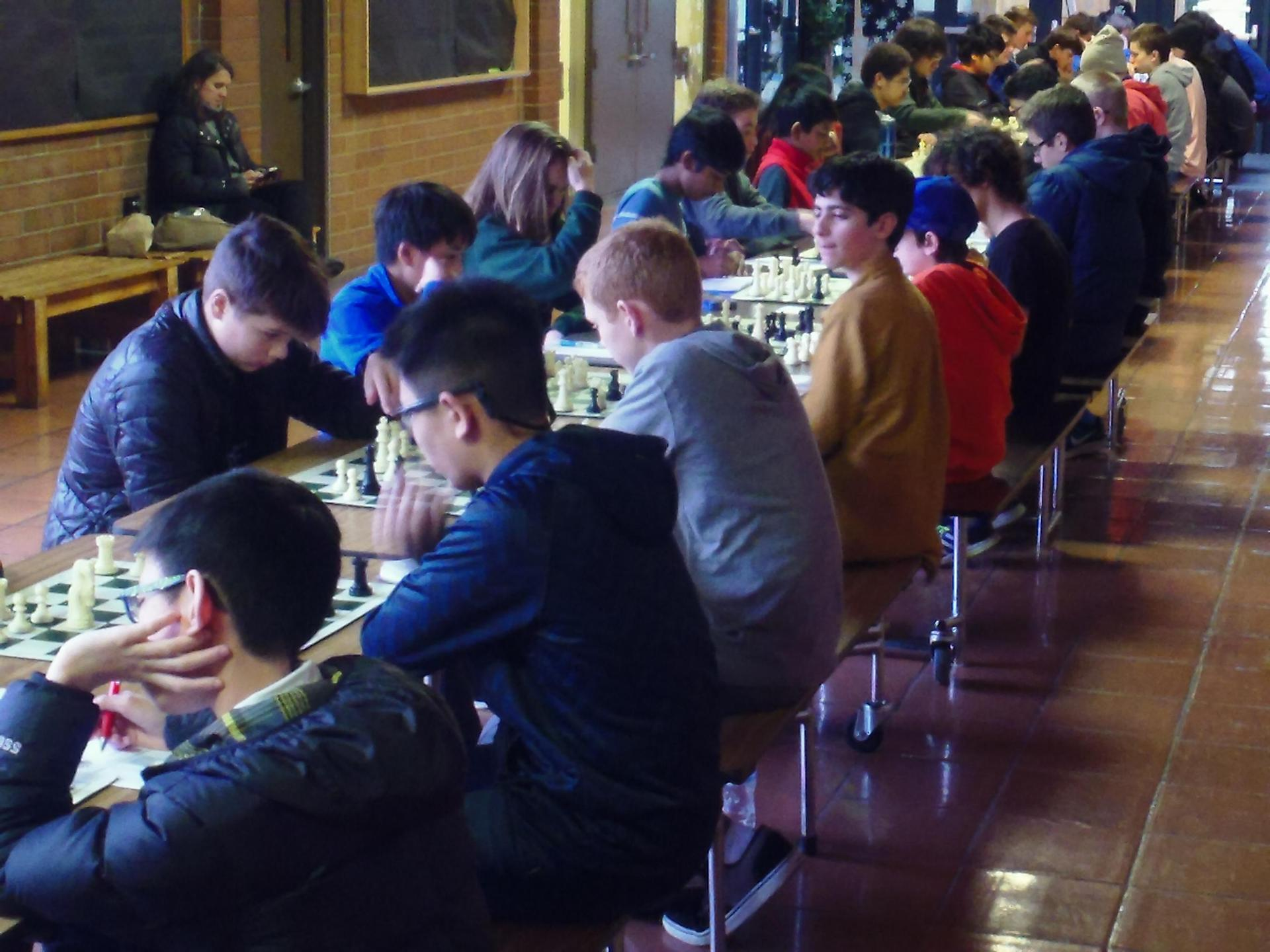 long row of tables of kids playing chess