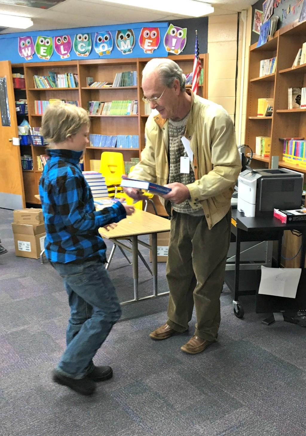 Rotary Club member handing out dictionary to student
