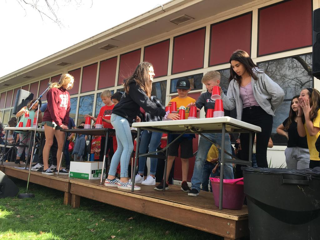 students playing cup game at assembly