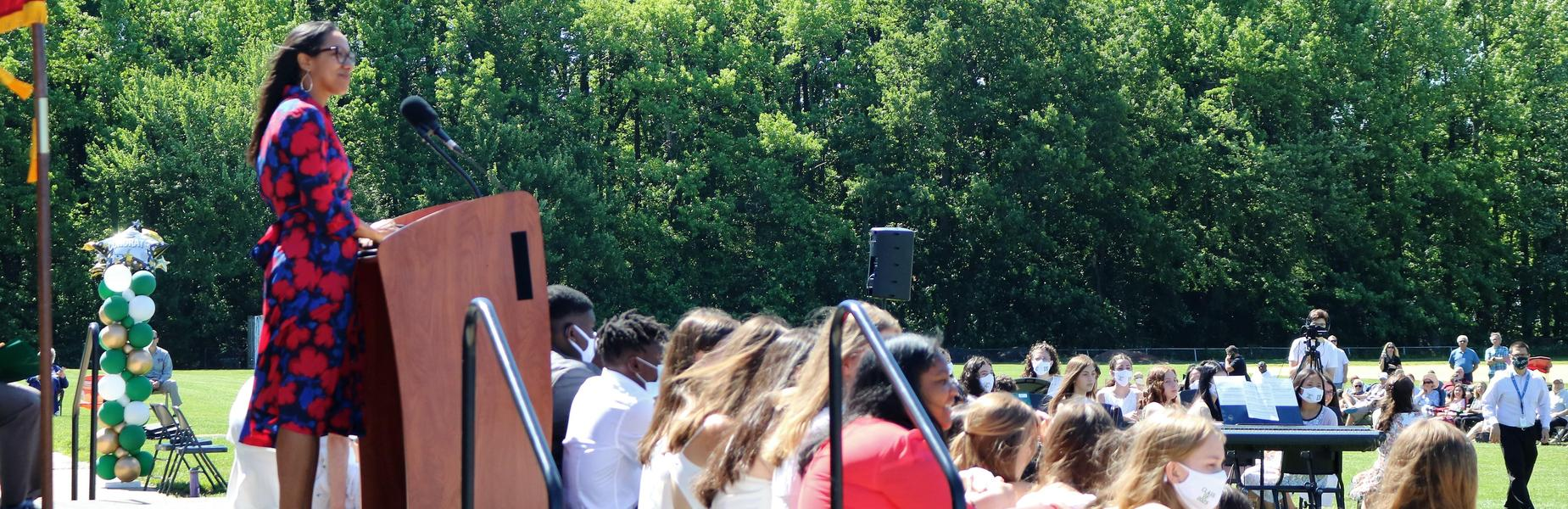 Photo of Edison Asst Principal Crystal Marsh addressing students and families during 8th grade promotion ceremony.