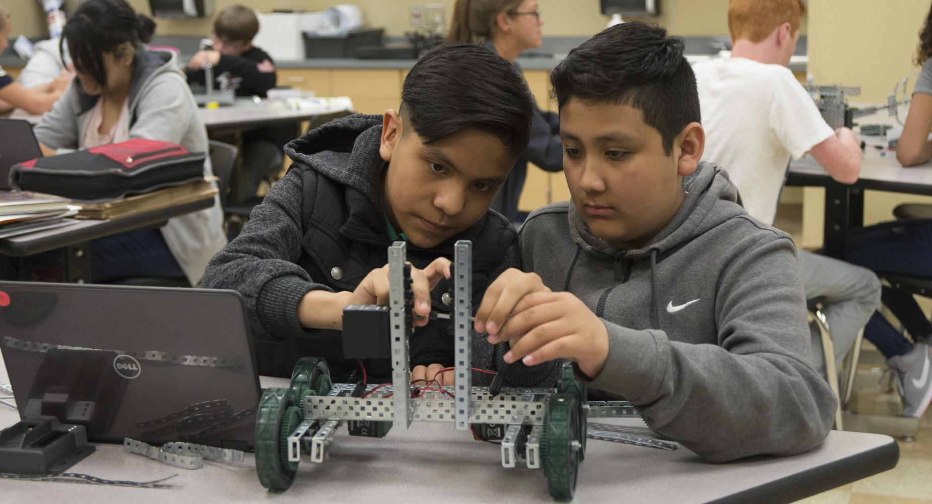 Two boys work on a robotics project