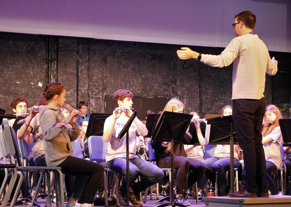 Photo of WHS band director working with high school and intermediate school student band musicians during District Music Day.