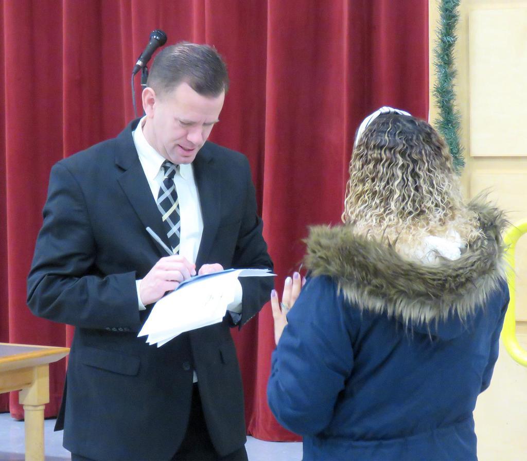 Principal David Brady makes notes as he talks to a parent