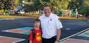 Wilson student poses for picture with special escort - a Westfield firefighter - on Walk to School Day.