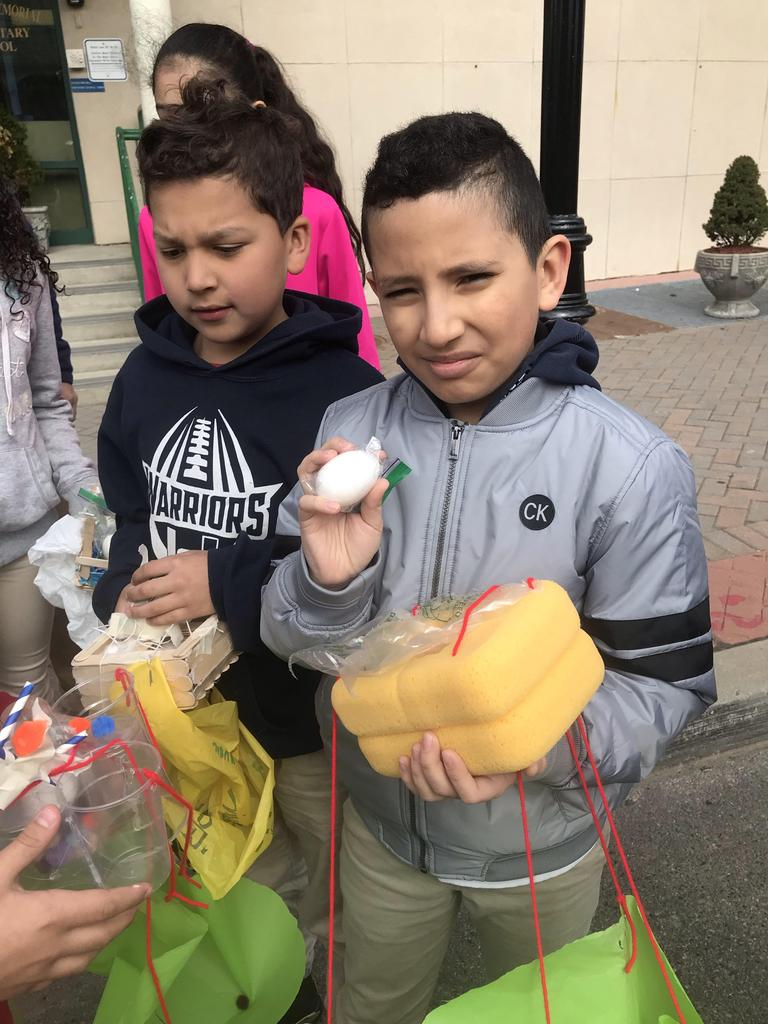 a boy holding his safe egg in his hand as he hold the two sponge container that protected the egg from the drop