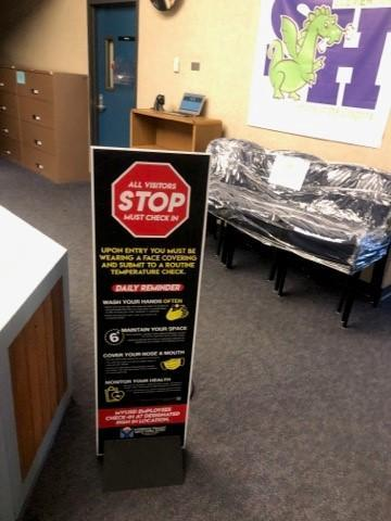 Tall entryway sign for COVID check-in