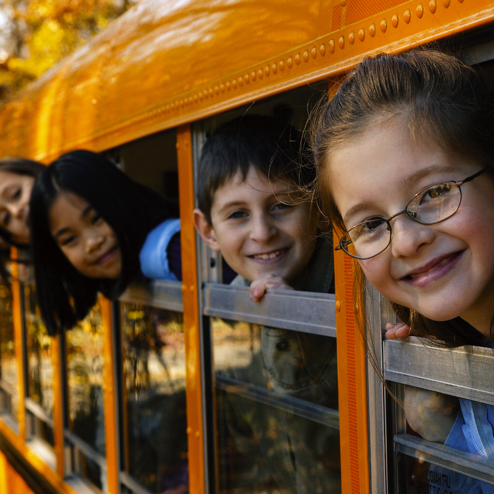 4 kiddos with smiling with their heads out of school bus windows