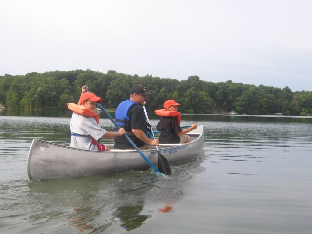 kids row boat on lake