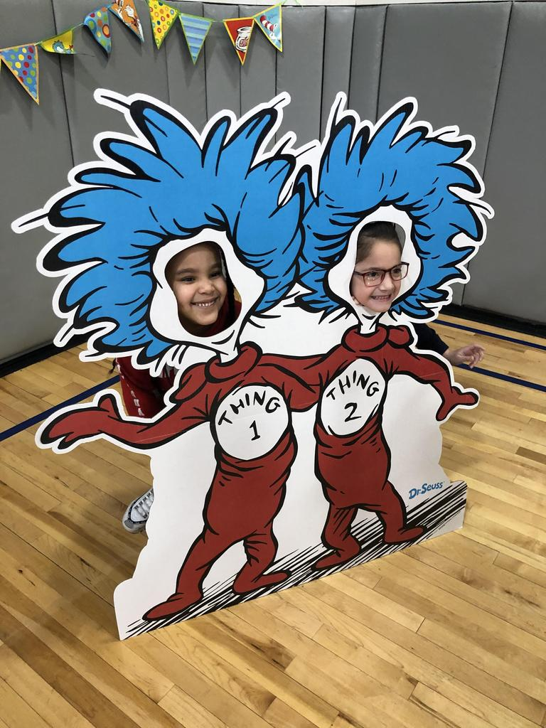 two children with their heads in a cardboard thing 1 & 2 pop up