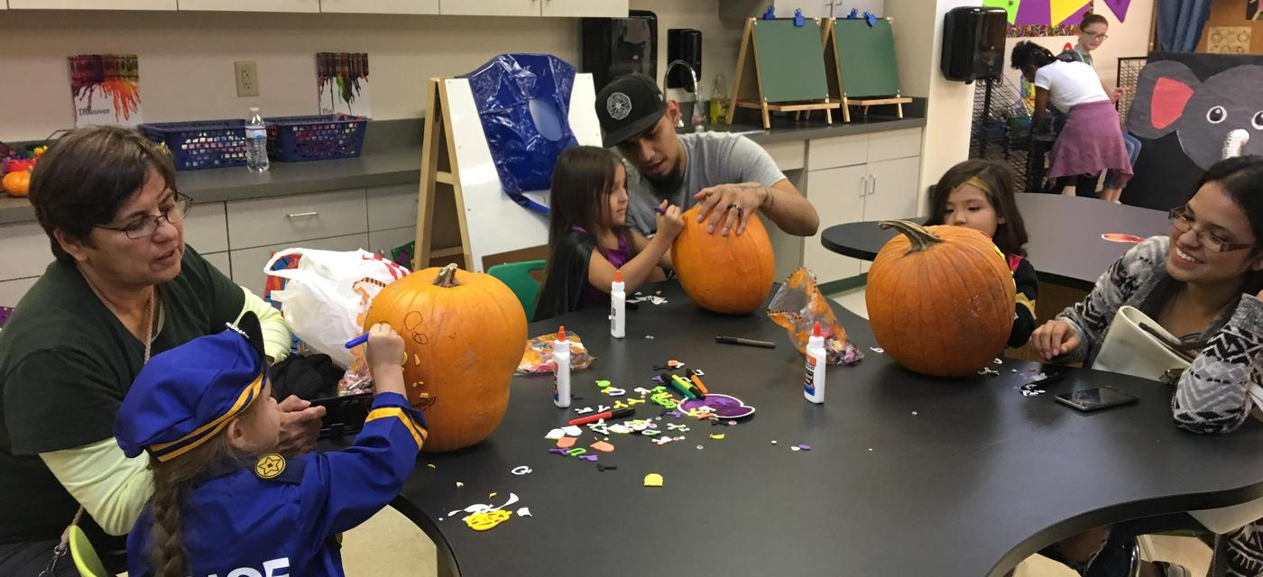 students and parents decorating pumpkins