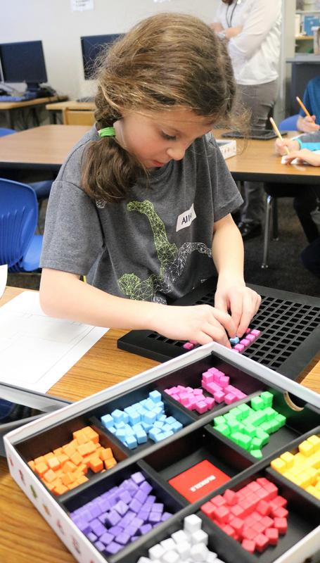 Second grader Allison McMullen graphs and designs characters and a game board for a computer video game during an afterschool STEAM class at Tamaques School.