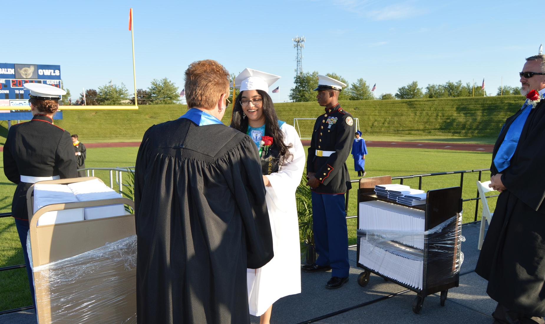 BHS female senior, wearing a white graduation cap and gown receives her diploma