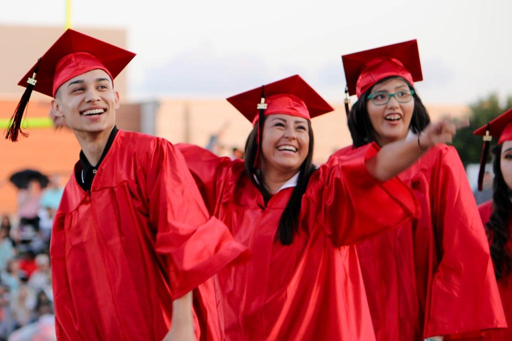 three victoria east high school students smile and cheer at their family and friends in the stands at the 2018 victoria east high school graduation ceremony