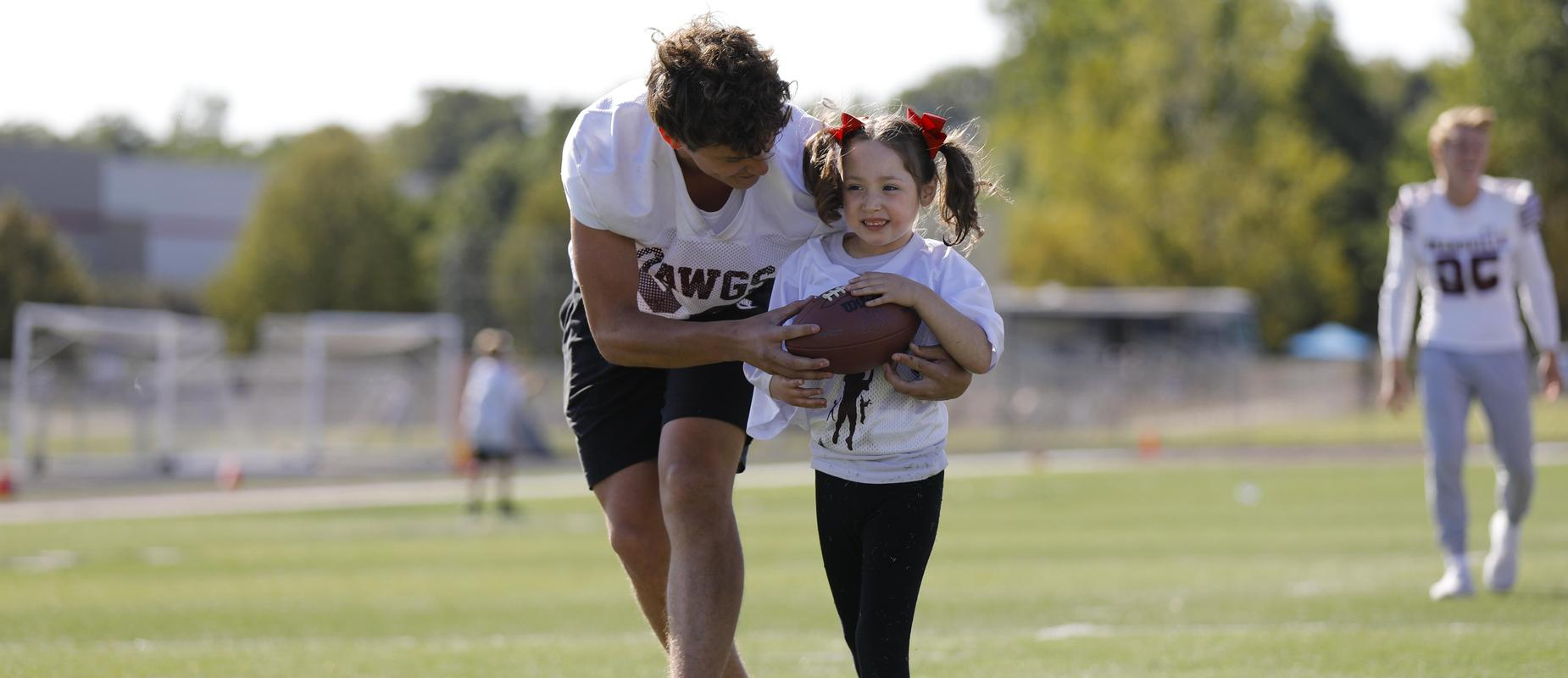 football player helps young girl cross into the endzone with football