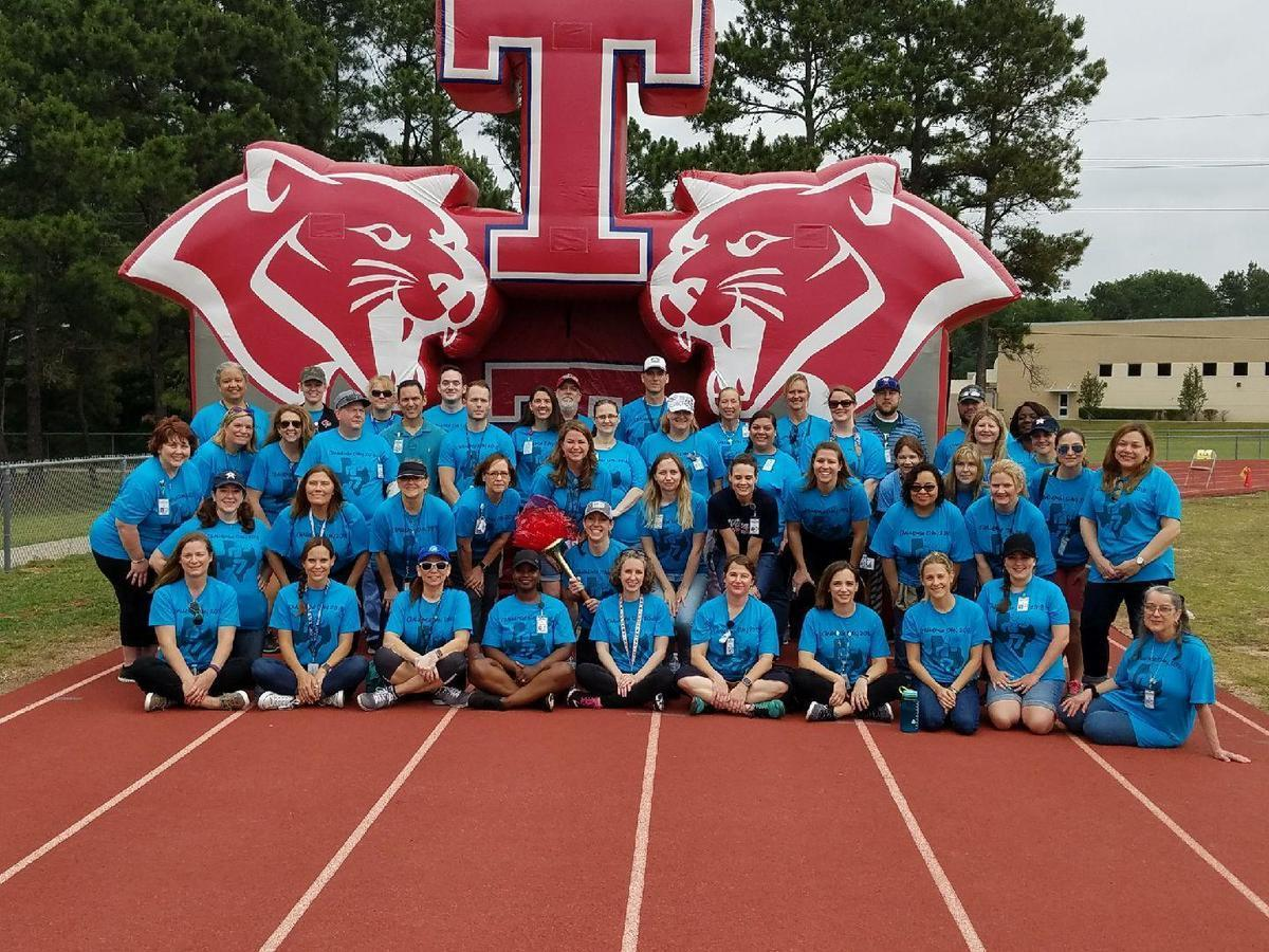 Student Support Personnel posed as a group in turquoise shirts in front of a blow up Cougar on a track