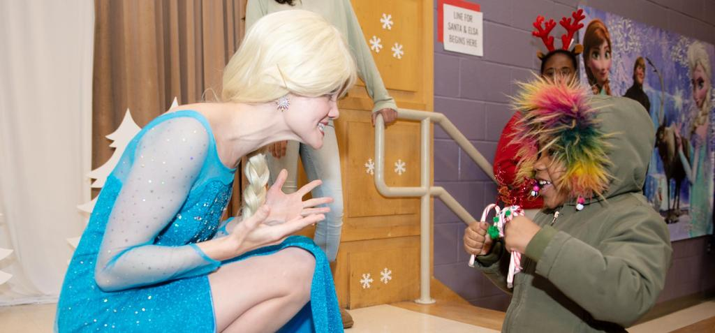 """Elsa from """"Frozen"""" looks on in wonder as a young student prepares her with two candy canes"""