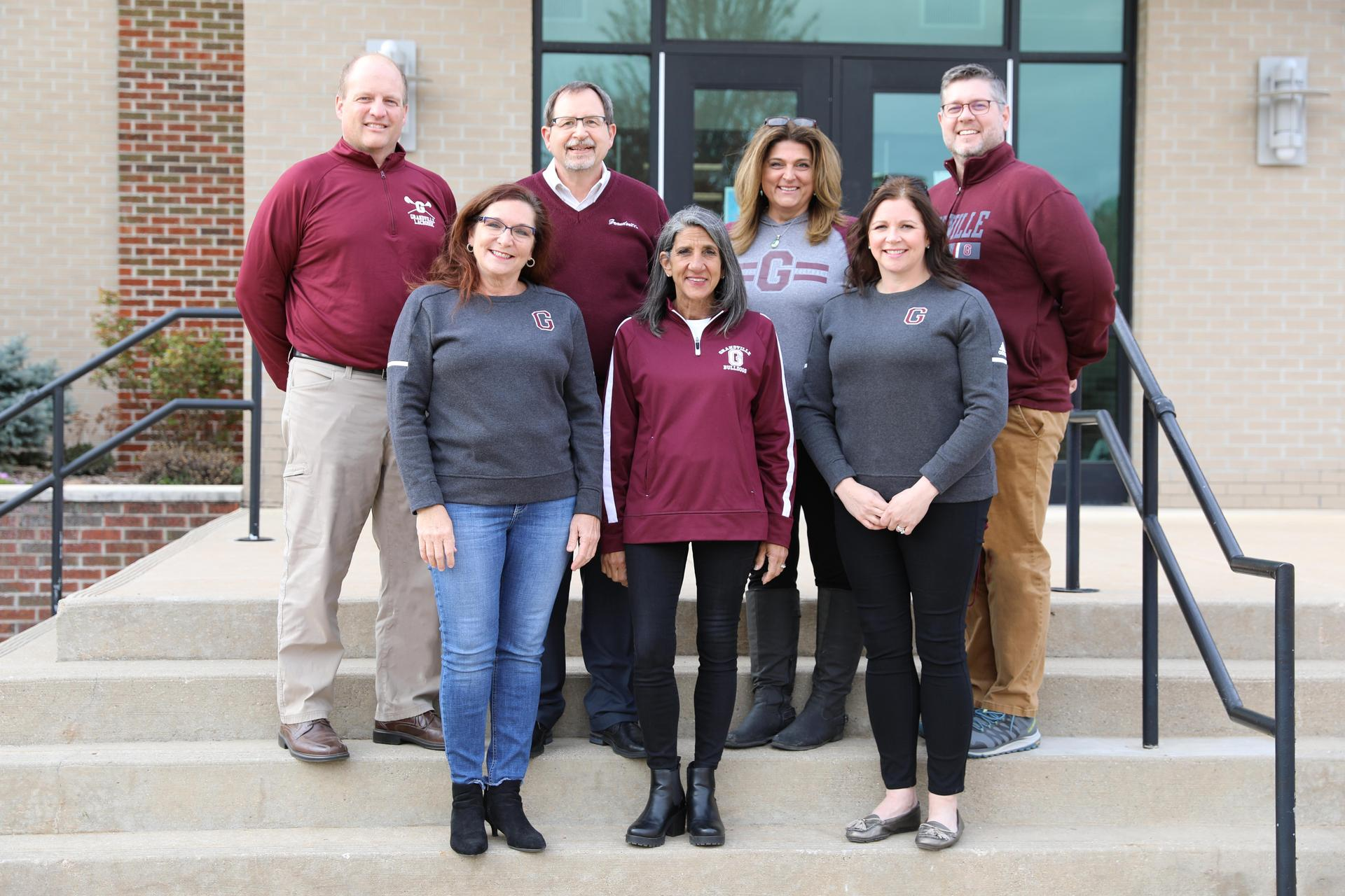 7 board members on steps outside in Grandville gear