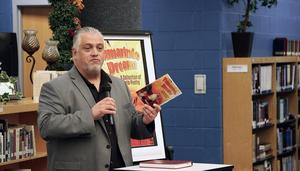 "Author Roberto Rocha holds his book ""Tamarindo Dreams: A Collection of Barrio Poetry,"" while visiting with students at Edinburg High School."