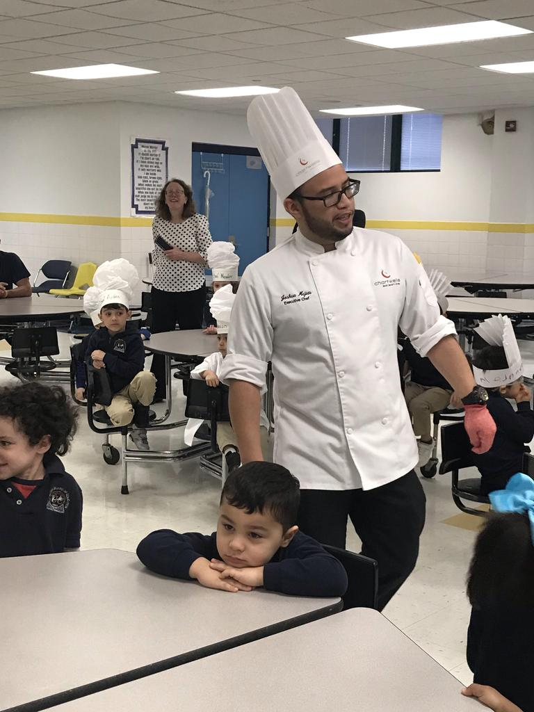 Chef Josh walking around students with principal O'Connel in the background