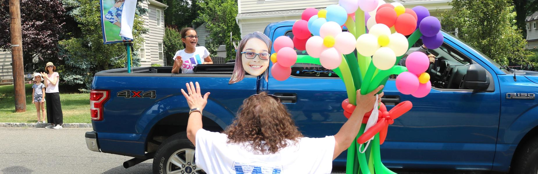 Photo of Wilson teacher with balloon bouquet waving at 5th grader during Grade 5 Clap Out Car Parade.