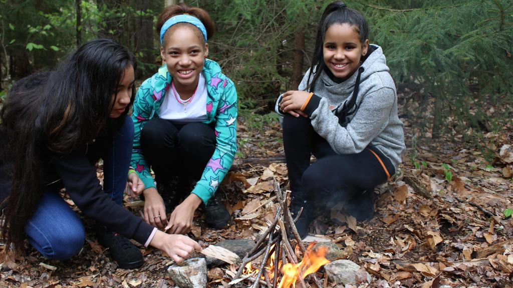 3 girls building a fire.