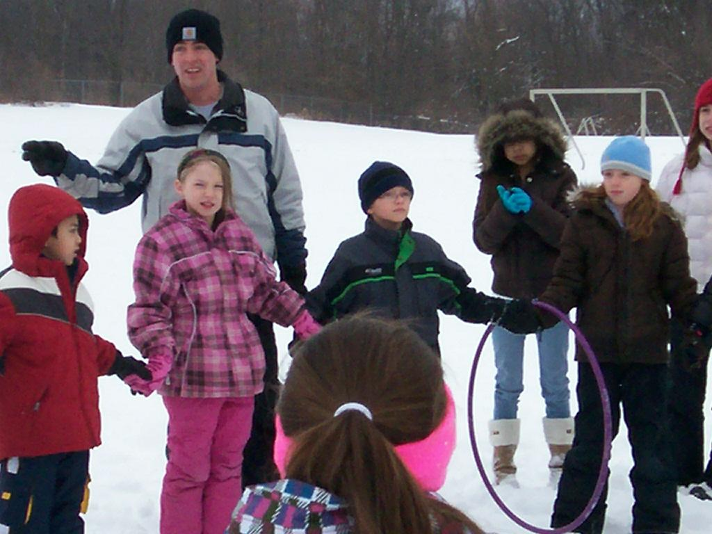 kids outside in snow at recess with male teacher giving directions