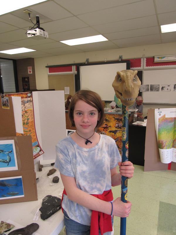 pic of girl posing with dinosaur head model