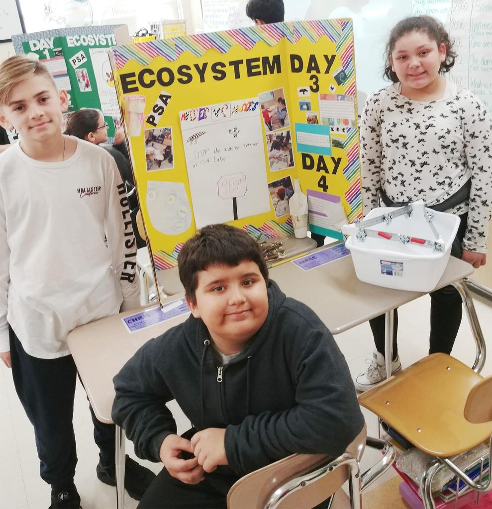 Three Keverian School fifth graders stand in front of their STEM project on ecosystems